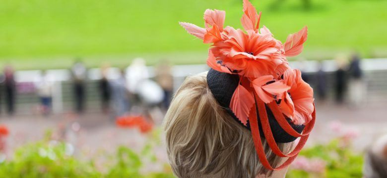A stylishly dressed lady at the racecourse, watching thoroughbred race horses in a flat race on turf,as they pass in front of the grandstand on a summer's day.