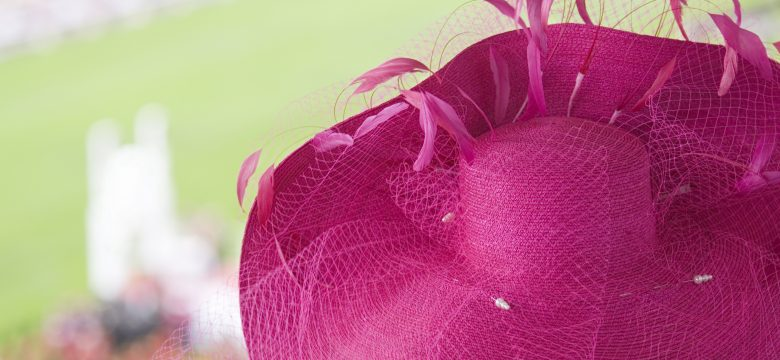 """A fashionable stylish, bright pink, straw, netting and feather ladies hat. The lady wearing this fabulous hat is watching the prize giving ceremony to the winning owner, trainer and jocke, at the Longchamp horse race track in the Bois de Boulogne, Paris. Good Copy space."""