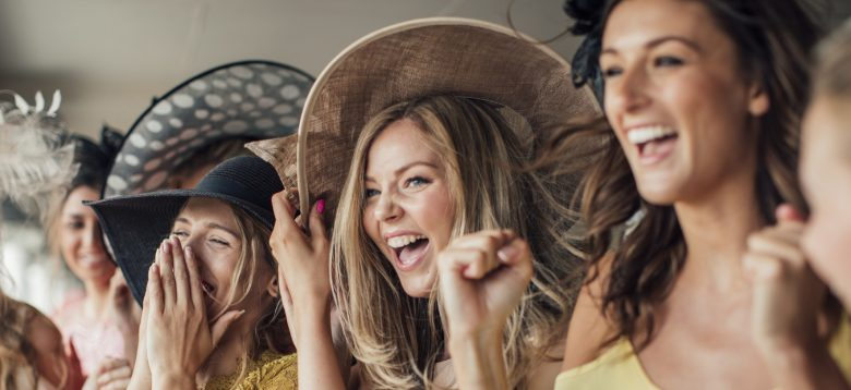 A group of young women wearing designer hats cheering on for the running horses on ladies day.
