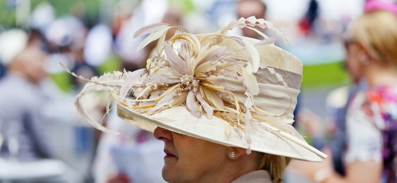 A stylish lady with an elegant summer hat, at the racetrack at Chantilly on Ladies Day for the Prix Diane, enjoying a glass of champagne.