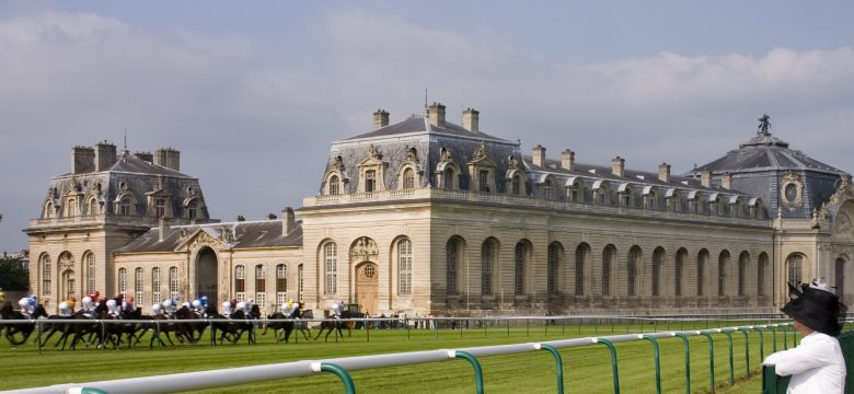 """On the public parkland at the stylish and fashionable horse racing centre of Chantilly, France, racing takes place in front of the Living Horse Museum, Le Musee Vivant du Cheval, which houses the worldaas most beautiful stables, and probably the largest at 186mm long. They were built in 1719, could house up to 240 horses and belonged to the adjacent, Chantilly Chateau which was in the ownership of the Princes de CondA. PLEASE NOTE: The pattern of the fabric on the ladies dress has been bastardised."""