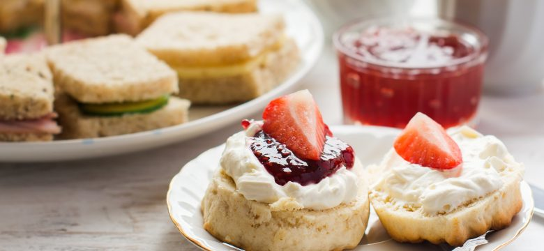 Traditional English afternoon tea: scones with clotted cream and jam, strawberries, with various sadwiches